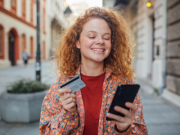 Girl holding credit card and phone making online payment