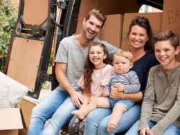 Family sitting in van with moving boxes