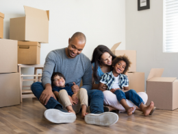 Family sitting on floor with moving boxes