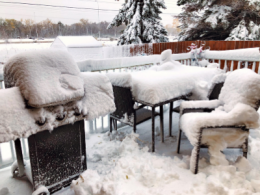 BBQ and patio furniture covered in snow