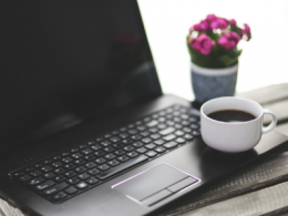 Laptop on table with cup of coffee and plant